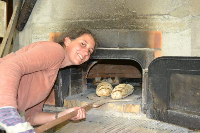 dans sa boulangerie artisanale la boulangère défourne des pains au levain cuit dans un four à bois