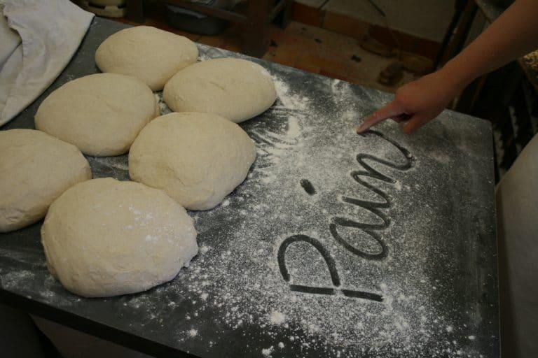 """Sur le plan de travail enfarinéde sa boulangerie artisanale, la boulangère trace avec son doigt le mot """"pain"""". Des pâtons sont posés à côté, pendant le temps de la détente."""