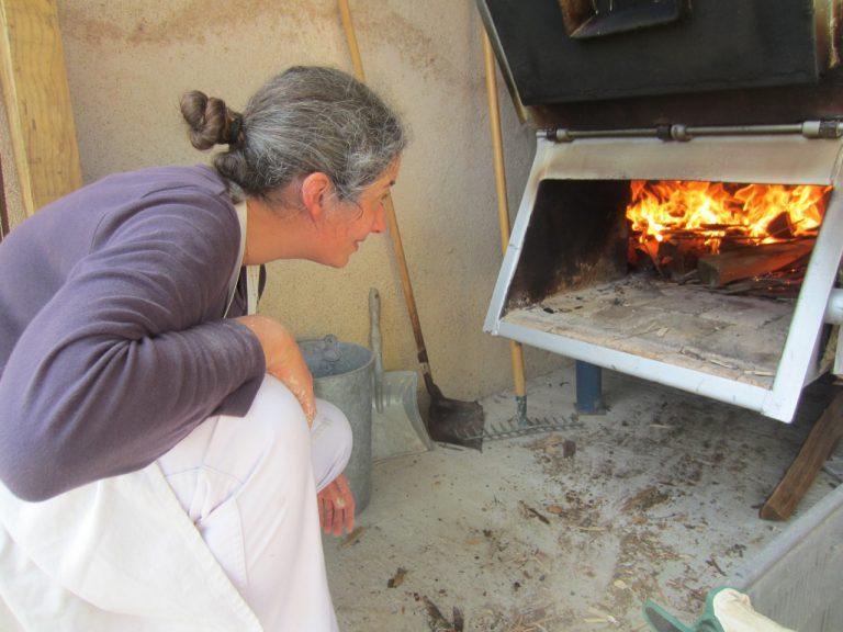 la boulangère examine accroupie le feu de son four à pain de sa boulangerie artisanale à montpezat d'agenais dans le 47