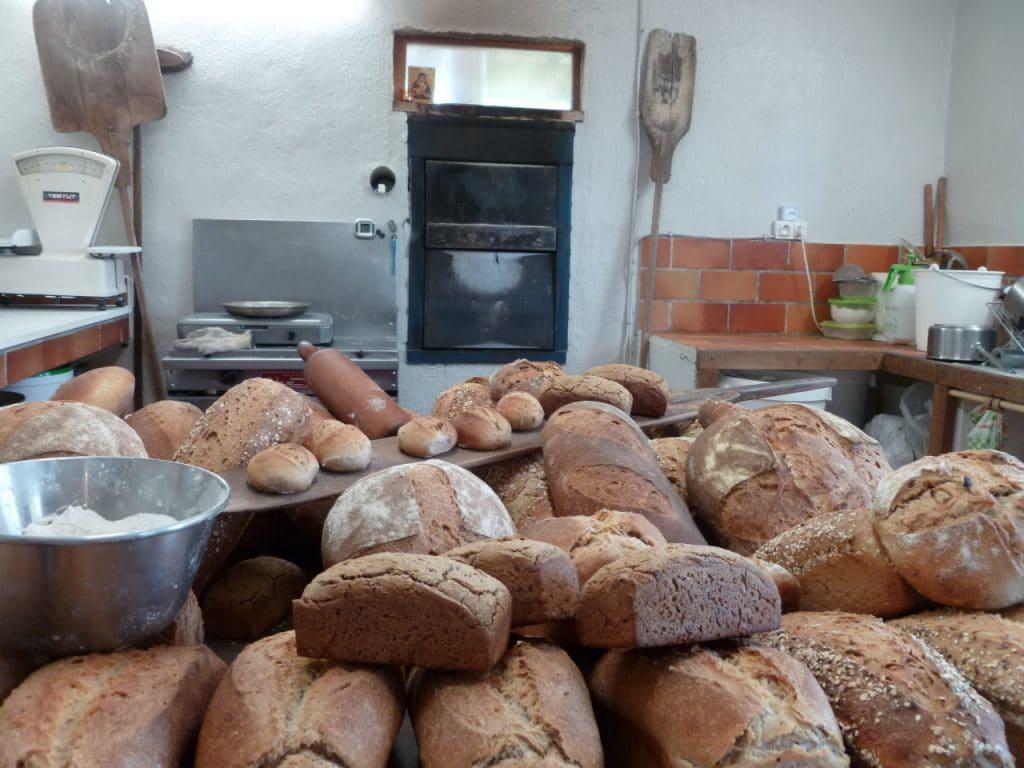 À l'intérieur du fournil Soleil levain on voit les pains sortis du four entassé en une jolie colline où on apperçoit aussi la farine et la pelle à enfourner. Une balance ancienne trône sur le plan de travail.