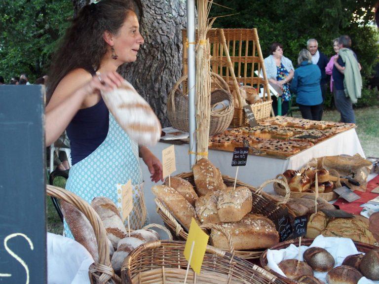 la boulangère vend son pain au levain bio au marché de producteurs de pays