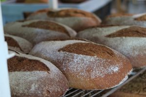 ces pains complets à base de farines bio de blés anciens reposent sur une grille à la sortie du four