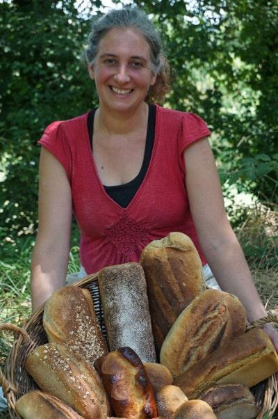 boulangère qui tient une panière de pains au levain sur fond de nature du Lot et Garonne