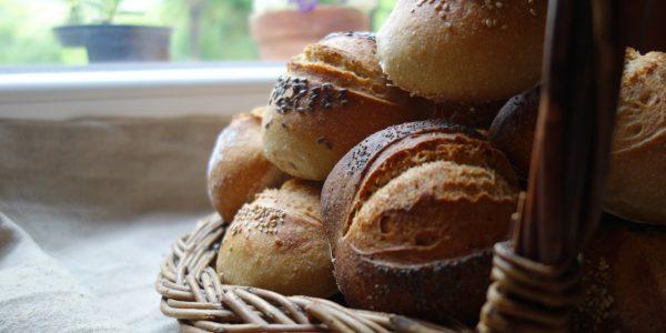 le petits pains individuels sont empilés dans un panier à anse, devant une fenêtre, ils sont décorés avec des graines de sésame, lin, pavot